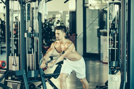 bare chest: Handsome young man with muscular wet body and bare chest training with heavy exercise equipment in gym