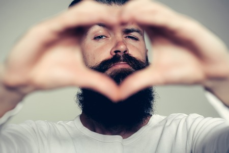 long beard: handsome young man with long beard and moustache on face holding hands in heart shape on grey background in studio