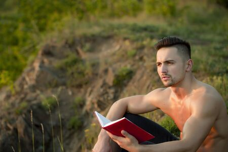 bare chest: Young handsome man with muscular body and bare chest sitting with book outdoor sunny day