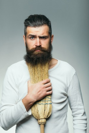 white beard: Bearded man with serious sad face in white shirt holding broom as beard in studio on grey background