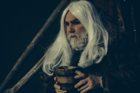 manteau de fourrure: Druid vieil homme avec de longs cheveux gris et barbe en manteau de fourrure avec la tasse en bois dans les mains sur fond sombre Banque d'images