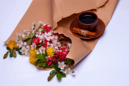 packing paper: Bouquet of spring flowers and cup of coffee on brown packing paper isolated on white background Stock Photo