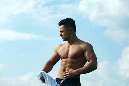 undressing: young macho man model athlete with muscular body and wet bare chest outdoor on sky background undressing white shirt