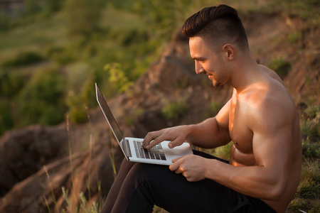 bare chest: Young handsome smiling man with muscular body and bare chest sitting with laptop outdoor sunny day Stock Photo