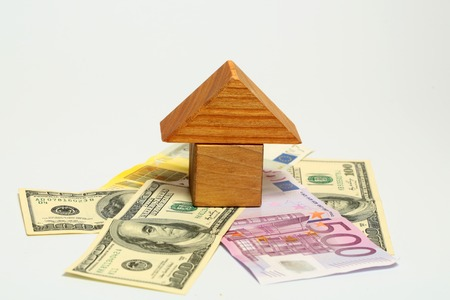 morgage: wooden toy house over euro and dollar banknote isolated on white background.