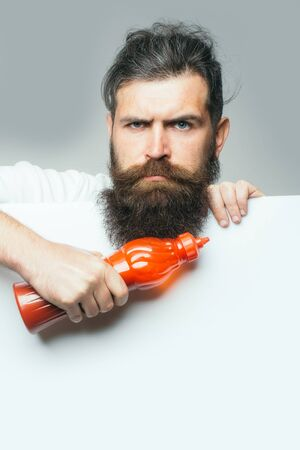 ketchup bottle: handsome bearded man with long lush beard and moustache on serious face holding red plastic ketchup bottle with paper sheet on grey background Stock Photo