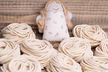 rag doll: Homemade tagliatelle and beautiful rag doll on wooden background