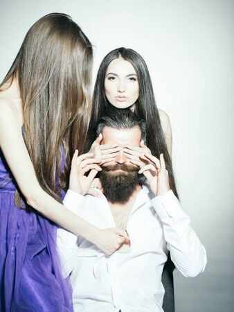 Bearded handsome man in white shirt with two young pretty women in violet dresses with long hair closing eyes in studio on grey background 免版税图像