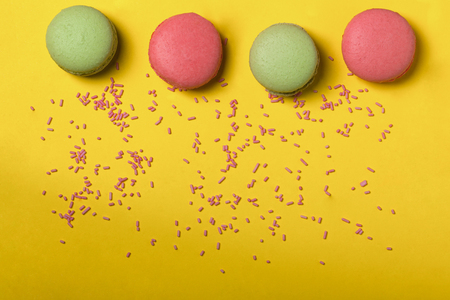 dragee: Colorful macaron pink and green color drop with many small dragee candies sprinkles on yellow background