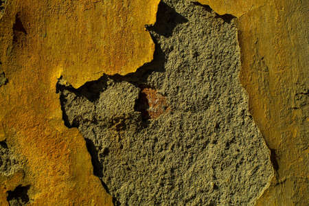 uneven: Textured backdrop of old plaster wall with yellow uneven aged paint Stock Photo