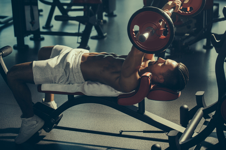 tricep: Handsome young man with muscular wet body bare torso and chest training with heavy barbell in gym Stock Photo
