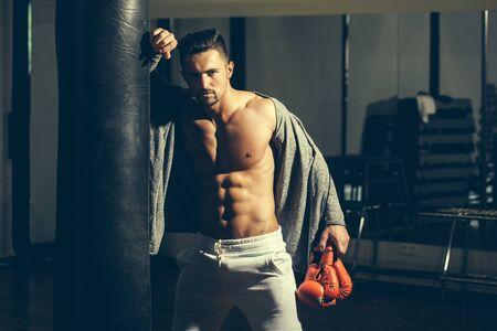 nackte brust: Gut aussehender junger Mann mit muskulösen Körper nackten Oberkörper und Brust in der Nähe von Boxsack in Boxhandschuhen Lizenzfreie Bilder
