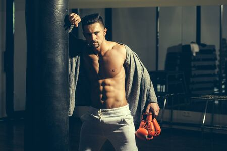 bare chest: Handsome young man with muscular body bare torso and chest near punching bag in boxing gloves