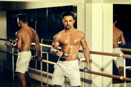 tricep: Handsome young man with muscular wet body bare torso and chest training with heavy dumbbell in gym