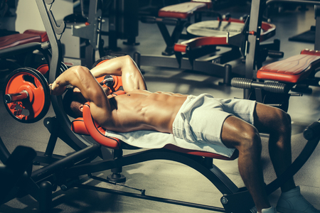 bare: Handsome young man with muscular wet body bare torso and chest training with heavy barbell in gym Stock Photo