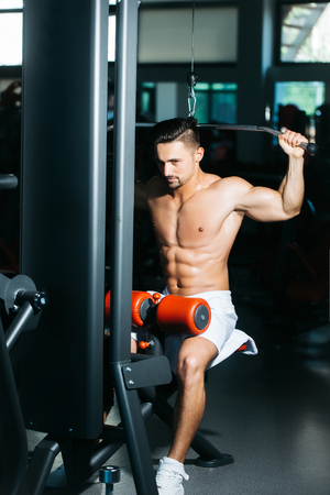 nackte brust: Handsome young man with muscular wet body and bare chest training with heavy exercise equipment in gym