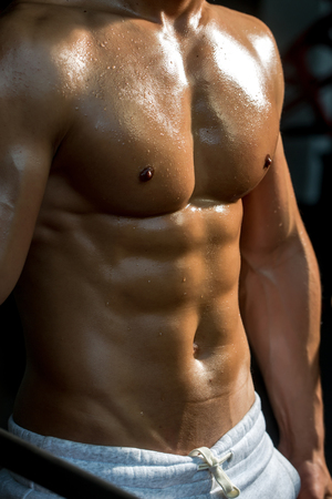 six packs: muscular male torso six packs on wet body of athletic man training with bare chest and strong biceps on hands, closeup