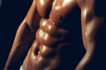 nackte brust: muskul�sen m�nnlichen Sixpacks auf nassen K�rper des athletischen Mannes Training mit nackten Brust und starken Bizeps auf H�nden Torso, Nahaufnahme