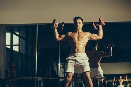 hombre deportista: Apuesto joven con cuerpo muscular húmedo torso desnudo y la formación pecho con mancuerna pesada en el gimnasio