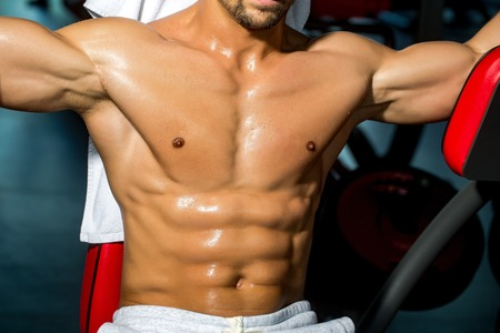 six packs: sexy muscular male torso six packs on wet body of athletic man training with bare chest and strong biceps on hands, closeup