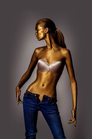 bodyart: Golden female body of young sexy beautiful woman with bare belly in bra and blue jeans on grey background. Metallic art, body art