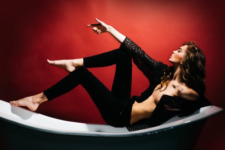 lying in bathtub: Sexy beautiful young woman with long lush curly hair pretty face and slim body with bare belly lying on bathtub on red background