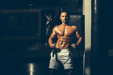 nackte brust: Gut aussehender junger Mann mit sexy muskulösen Körper nass nackten Oberkörper und Brust hält Seil springen Lizenzfreie Bilder