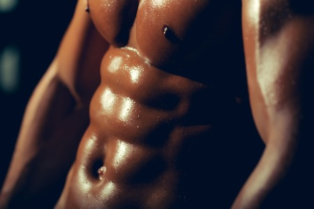 nackte brust: sexy muskulösen männlichen Sixpacks auf nassen Körper des athletischen Mannes Training mit nackten Brust und starken Bizeps auf Händen Torso, Nahaufnahme