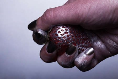 crumple: female hand crumple strawberry covered with silver paint with seed texture on grey background closeup