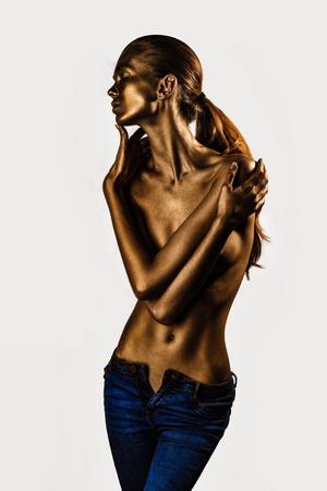 nackte brust: Goldene weibliche Körper der jungen sexy schöne Frau mit nackten Brust und Bauch auf weißem Hintergrund. Metallic Kunst, Körperkunst