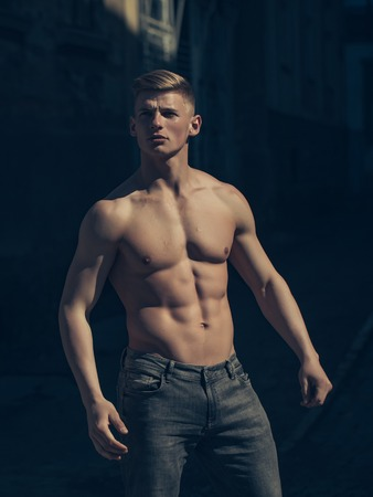 barechested: Man bare-chested young pose sexy model in jeans outdoor near building sunny day outdoor Stock Photo