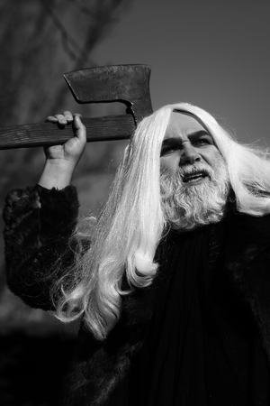 grey  sky: Brutal druid old man with long silver hair and beard in fur coat with axe in hand black and white on grey sky background