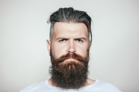 long beard: handsome young man with long beard and moustache on serious face on grey background in studio