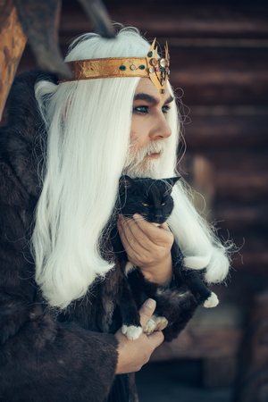 druid: Druid old man with long grey hair and beard with crown in fur coat holds cat on dark wooden background