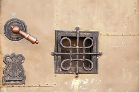 doorknob: Small square wrought iron grating window and doorknob on metal armor texture background closeup Stock Photo