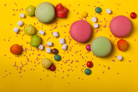 dragee: Colorful macaron pink and green color drop with many small jelly candies and dragee with marshmallow on yellow background Stock Photo