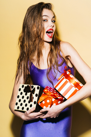 jumpsuit: young girl with pretty surprised smiling face in violet jumpsuit holding colorful boxes of presents standing on yellow background