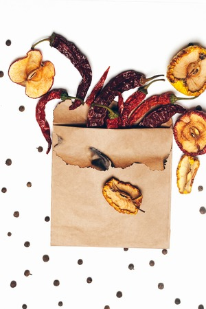 scorched: brown scorched paper envelope with dried red chilli pepper and allspice with wrinkled apples inside isolated on white background, copy space
