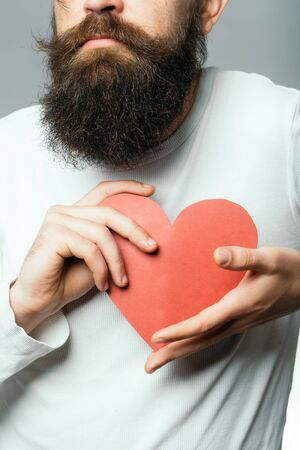 romantic man: bearded romantic man with long beard holding red paper heart in studio on grey background, copy space