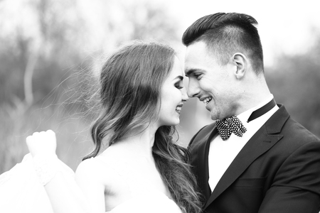 happy wedding: Beautiful bridal couple of young man embracing happy pretty woman outdoor, black and white