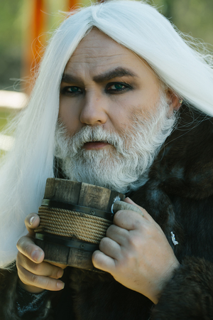 druid: Druid old man with wrinkles long silver beard and hair with wooden mug in hands on blurred background