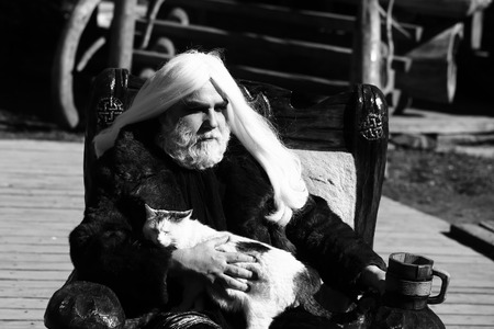 druid: Druid old man with long silver hair beard in fur coat sits in chair with cat and wooden mug black and white on grey background