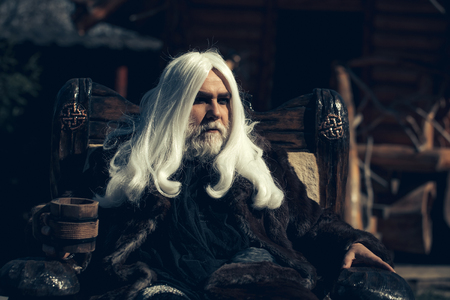sits on a chair: Druid old man with long silver hair beard in fur coat sits in chair with wooden mug on blurred background Stock Photo