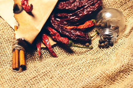 scorched: brown scorched paper envelope with dried red wrinkled chilli pepper inside with cinnamon and light bulb on burlap background, copy space