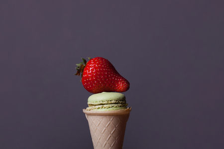 cookies and cream: Colorful macaron green color in ice cream cone of waffle on grey background with red juicy strawberry, copy space Stock Photo