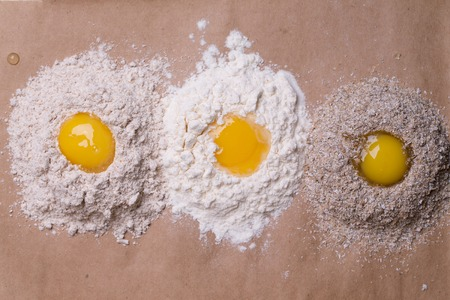 albumen: Three eggs broken and heaps of white and whole wheat flour bran ingredients for cooking food on brown paper background