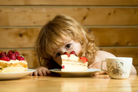 strawberry blonde: cute little boy child with long blonde hair eating tasty creamy pie or cake with red strawberry fruit on table with tea cup