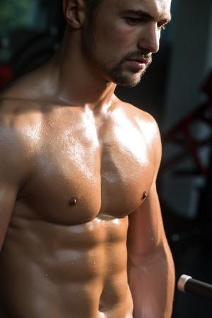 nackte brust: sexy muskul�sen m�nnlichen Sixpacks auf nassen K�rper des athletischen Mannes Training mit nackten Brust und starken Bizeps auf H�nden Torso, Nahaufnahme