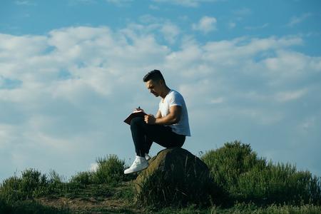 nackte brust: Junger stattlicher ernster Mann mit muskulösen sexy Körper und nackte Brust mit dem Laptop im Freien sonnigen Tag sitzen auf blauem Himmel Hintergrund