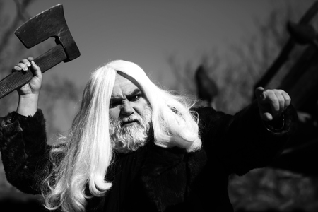 druid: Brutal druid old man with long silver hair and beard in fur coat with axe in hand black and white on grey sky background